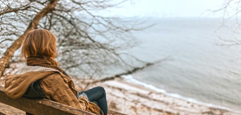 femeie singura pe o banca priveste marea
